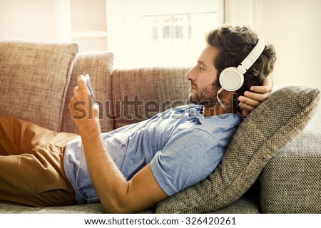 Man on couch watches a movie on mobile phone - stock photo
