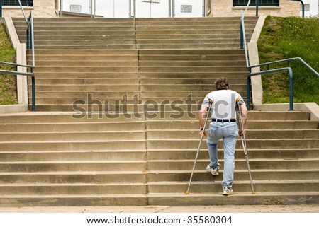 man on crutches climbs a big set of stairs - stock photo
