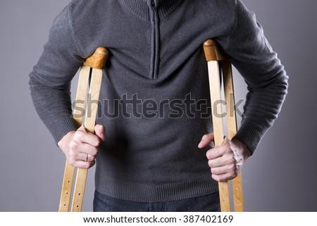 Man on crutches on a gray background. Studio shot - stock photo