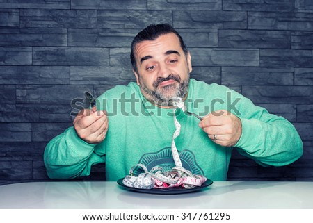 Man on diet, looking unhappy and disappointed, plate filled with measuring tape instead of food, diet and eating disorder concept - stock photo