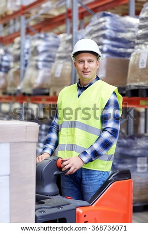 man on forklift loading boxes at warehouse - stock photo