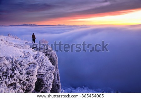 Man on frozen rocks standing over clouds looking at wonderful winter sunset on dark dramatically sky - stock photo