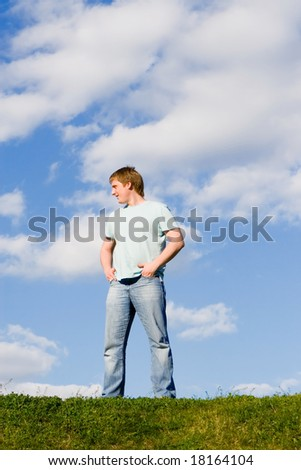 man on green grass and blue sky background - stock photo