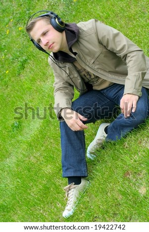 Man on green grass listens to music - stock photo