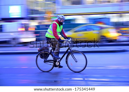 Man on his way home on bike, it's winter - stock photo