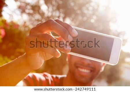 Man On Holiday Taking Selfie With Mobile Phone - stock photo