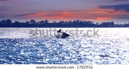 Man on jet ski at sunset - stock photo