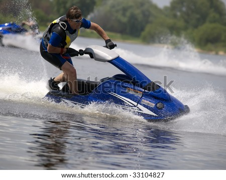 Man on jet ski in the river skim along very fast - stock photo
