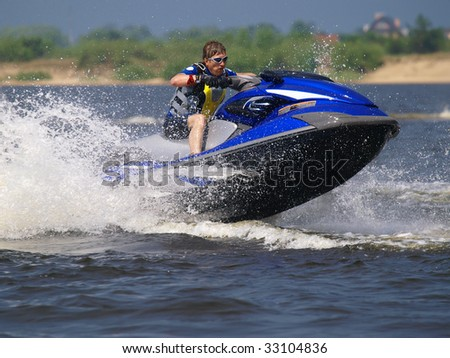 Man on jet ski jump on the wave - stock photo