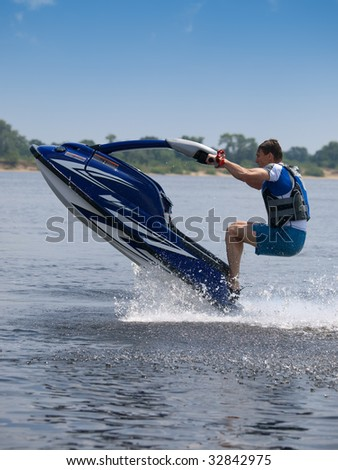 Man on jet ski jumps under the water - stock photo