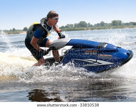 Man on jet ski rides very close - stock photo