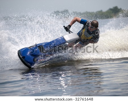 Man on jet ski turns left with much splashes - stock photo