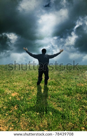man on knees in a meadow with open arms in a prayer gesture - stock photo