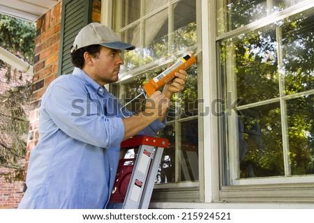 Man on ladder caulking outside window  - stock photo