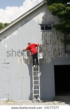 man on ladder painting barn wall - stock photo
