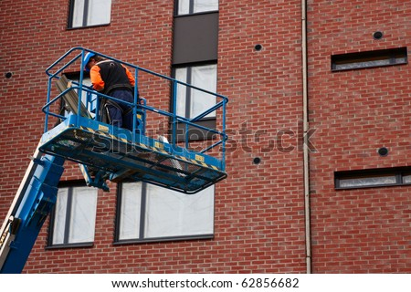 Man on lifting platform near building on construction site - stock photo
