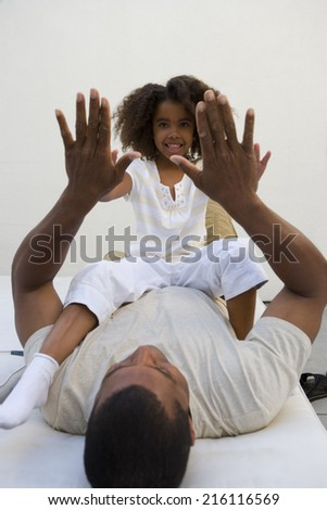 Man on lounge chair playing with daughter on lap - stock photo