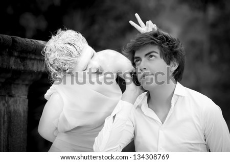 man on mobile phone and woman dressed as a statue having fun - stock photo