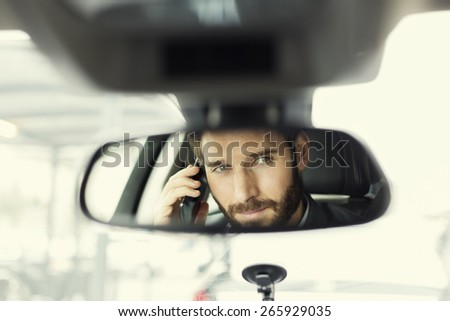 Man on mobile phone in the car. Reflection in the mirror - stock photo