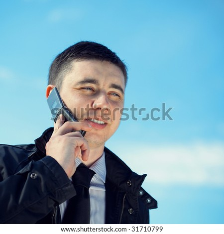 man on mobile phone on natural blue background