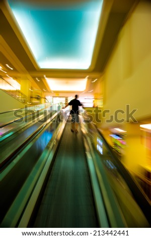 Man on moving staircase at shopping mall - stock photo