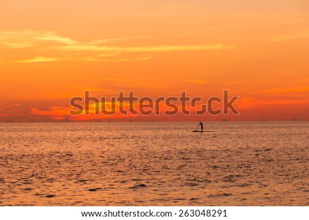 Man on paddle board at ocean sunset - stock photo