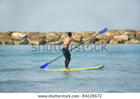 man on paddle board over sea - stock photo