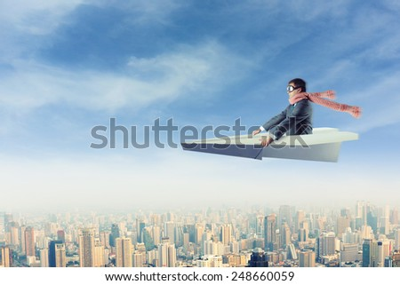Man on paper airplane above the city - stock photo