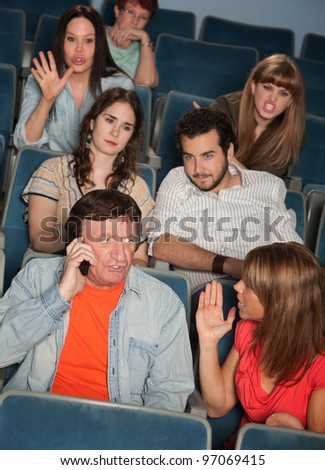 Man on phone call irks audience in theater - stock photo