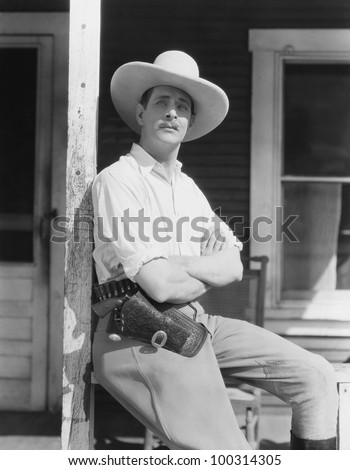 Man on porch wearing cowboy hat - stock photo