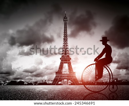 Man on retro bicycle next to Effel Tower, Paris, France. Black and white, vintage mood and red sun light - stock photo
