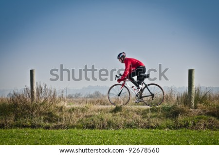 Man on road bike riding down open country road. - stock photo