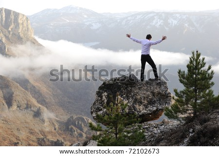 Man on rock against natural landscape - stock photo