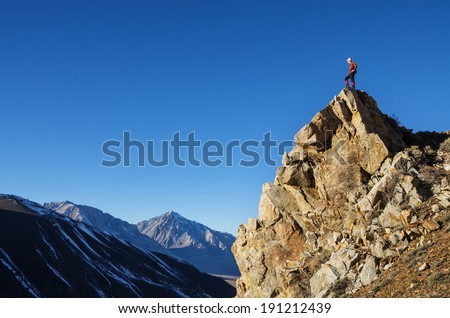 man on rocky peak looking across valley at distant mountains - stock photo