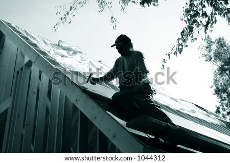man on roof installing tarpaper
