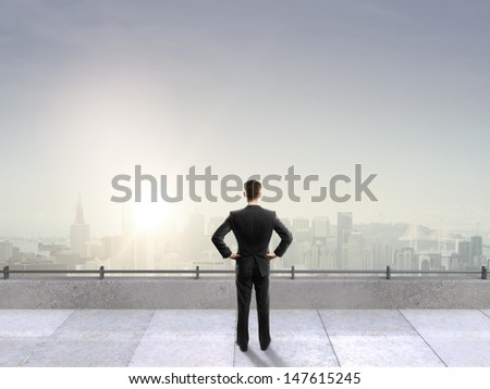 man on roof looking at city