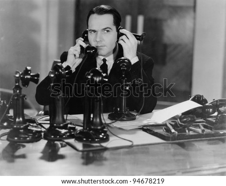 MAN ON SEVERAL PHONES - stock photo