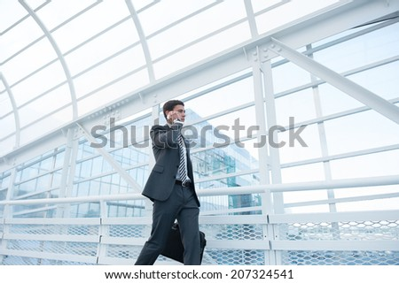 Man on smart phone - young business man in airport. Businessman using smartphone inside office building or airport.  - stock photo