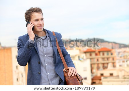 Man on smartphone - young business man talking on smart phone. Casual urban professional businessman using mobile cell phone smiling happy walking. Handsome man wearing suit jacket in Barcelona, Spain - stock photo