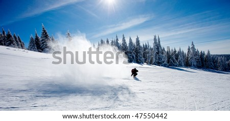 Man on snowboard making big splash of snow afret his trick - stock photo