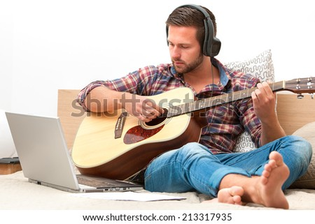 Man on sofa playing the guitar with laptop at home - stock photo