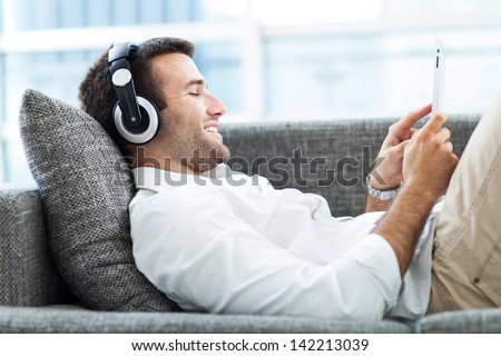 Man on sofa with headphones and digital tablet  - stock photo