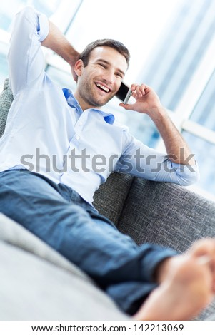 Man on sofa with mobile phone  - stock photo