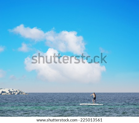 man on stand up paddle board - stock photo