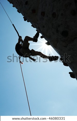 Man on steep climbing wall against blue sky