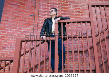 Man on steep staircase enjoying the view from his high perch. - stock photo