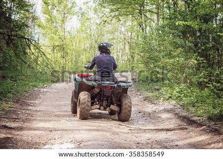 Man on the ATV Quad Bike on the mountains road.  - stock photo
