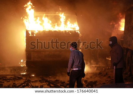 Man on the background of a burning bus. Kyiv, Ukraine, January 19, 2014