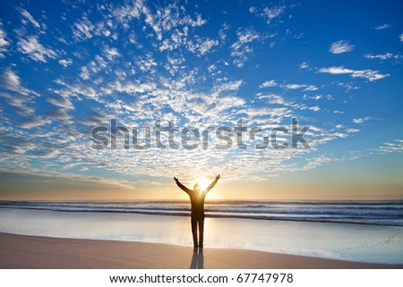 Man on the beach appreciate beautiful sunrise with his hands up - stock photo