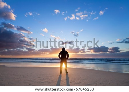 man on the beach in front of rising sun - stock photo